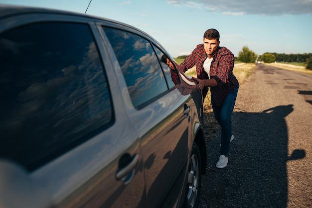 Uomo che spinge la macchina rotta. veicolo con trounble sul ciglio della strada nel giorno d'estate