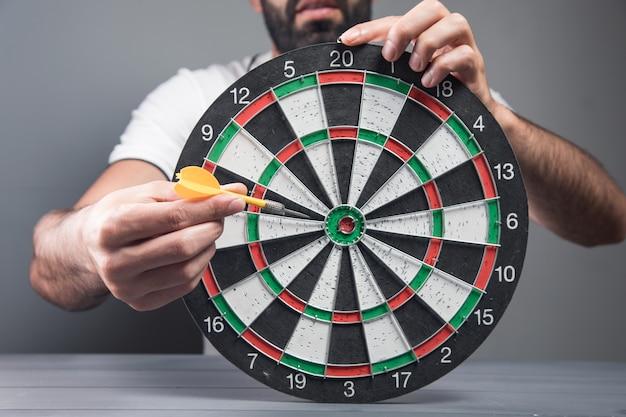 L'uomo mette la freccetta al centro del bersaglio. concetto di esecuzione degli obiettivi sul muro grigio