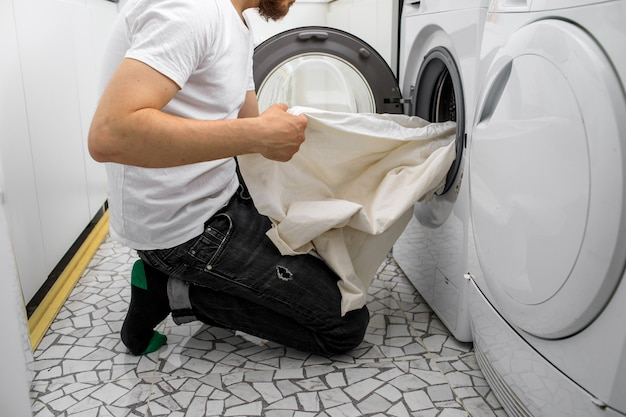 L'uomo mette il bucato in una lavatrice