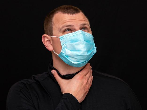 Un uomo si mette una maschera medica sul viso, istruzioni su come indossare una maschera