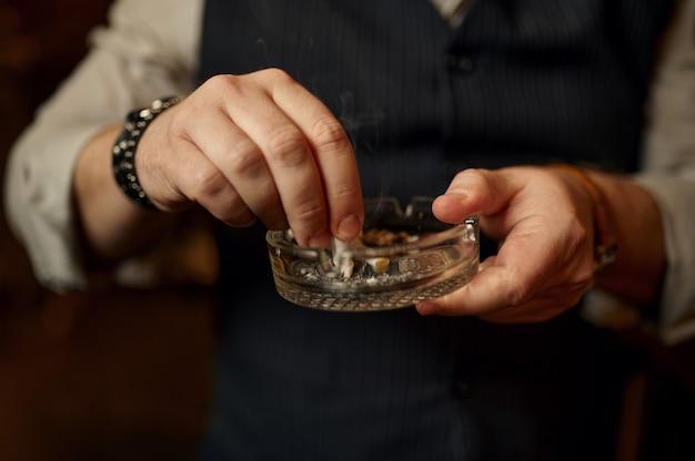 L'uomo spegne una sigaretta in un portacenere, vista del primo piano. cultura del fumo di tabacco, sapore specifico. svaghi fumatore maschio in ufficio