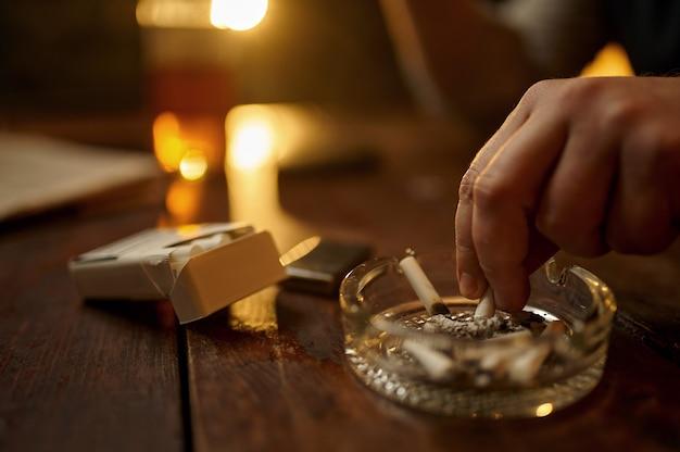 L'uomo spegne una sigaretta in un posacenere, primo piano. cultura del fumo di tabacco, sapore specifico. svaghi del fumatore maschio in ufficio