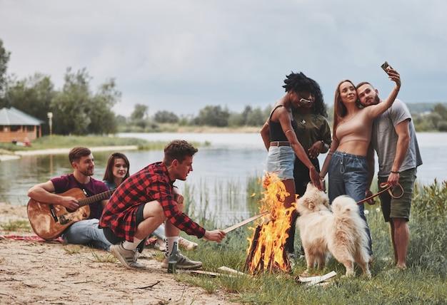 L'uomo mette la legna nel fuoco. un gruppo di persone fa un picnic sulla spiaggia. gli amici si divertono durante il fine settimana.