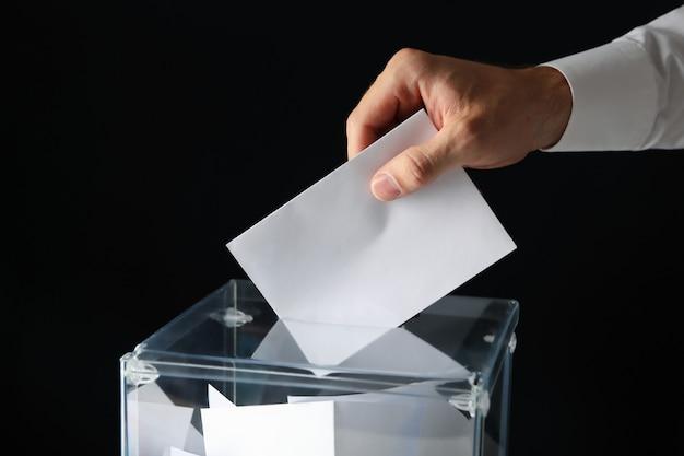 Uomo che mette scheda elettorale nella casella di voto sulla superficie nera