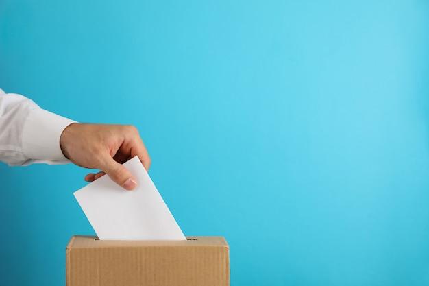 Uomo che mette scheda elettorale nella casella di voto sulla superficie blu