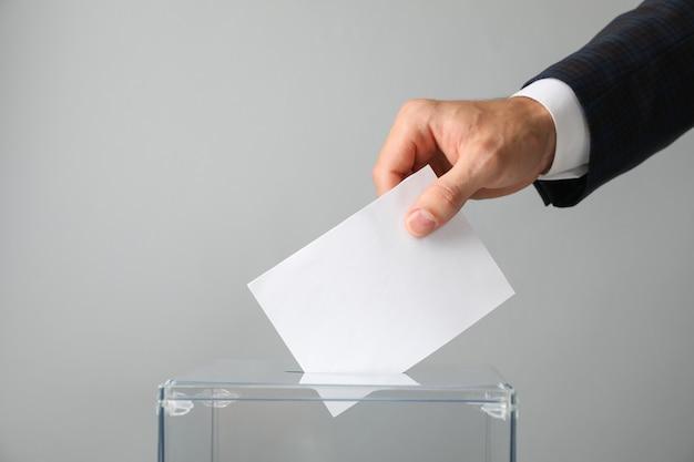 Uomo che mette scheda elettorale nella casella di voto sulla superficie grigia