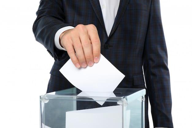 Uomo che mette scheda elettorale nella casella di voto