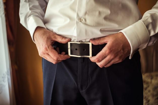 Uomo che indossa una cintura, uomo d'affari, politico, stile uomo, mani maschili primo piano, uomo d'affari, uomo d'affari, un uomo d'affari dall'asia, persone, affari, moda e concetto di abbigliamento