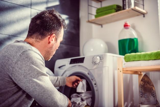 Uomo che mette i vestiti in lavatrice