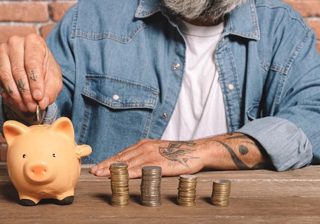 Uomo che mette le monete nel salvadanaio con la pila di monete sul tavolo per risparmiare denaro e concetto finanziario