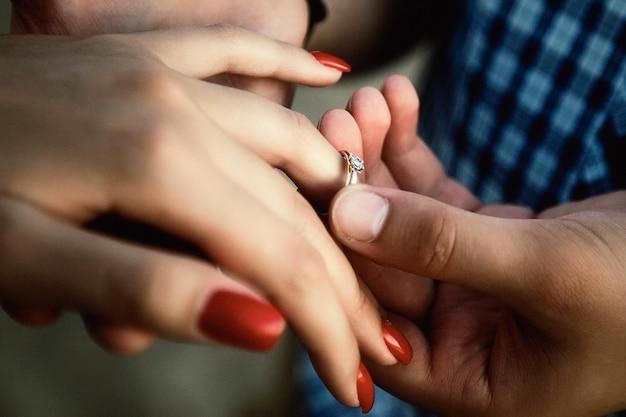Uomo che mette sul primo piano dell'anello di fidanzamento del dito della ragazza. fidanzato che mette l'anello al dito della ragazza. il maschio propone di sposarlo. felicità, relazioni, amore, concetto di fidanzamento. copia spazio per il sito