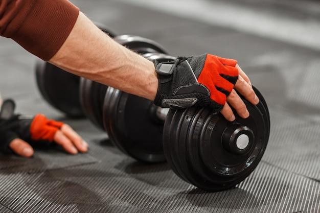 Uomo che mette la mano sul manubrio sul pavimento della palestra