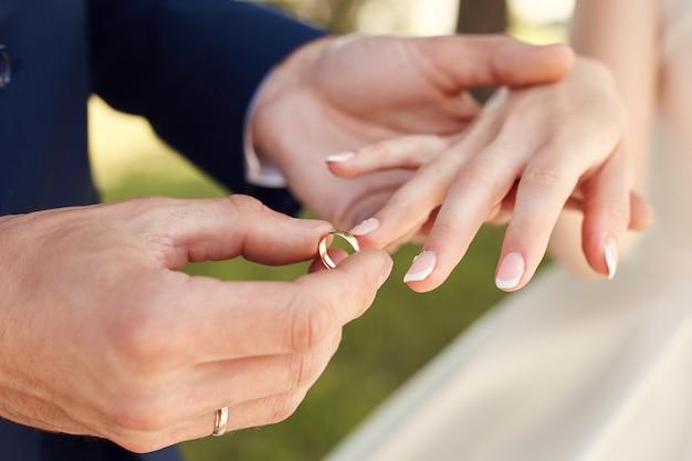 Uomo che mette un anello di nozze su un dito di donna