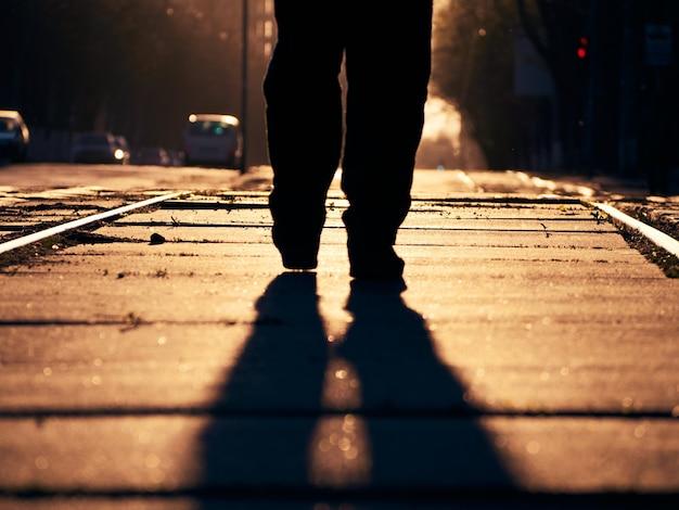 Uomo sui binari al tramonto