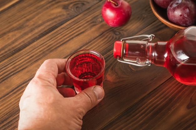 Un uomo solleva un bicchiere di liquore alla prugna su un tavolo di legno