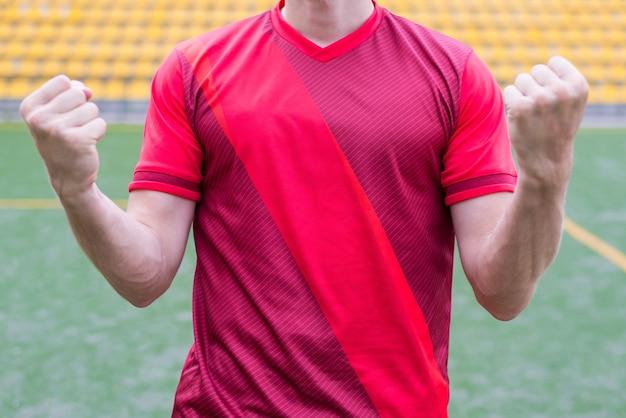 Uomo che alza i pugni sullo sfondo dello stadio