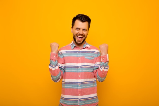 Uomo alzando i pugni con sorridente viso felice, sì gesto, che celebra il successo