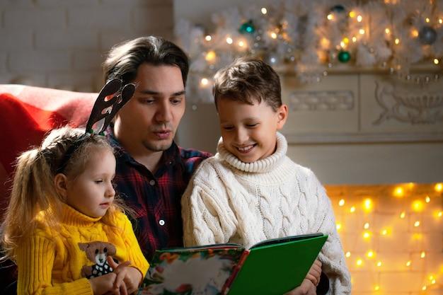 Uomo che legge un libro a un ragazzo e una ragazza