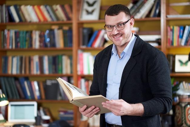 Libro di lettura dell'uomo nella biblioteca dell'istituto universitario molti libri