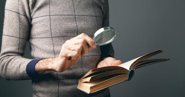 Uomo che legge un libro utilizzando una lente d'ingrandimento