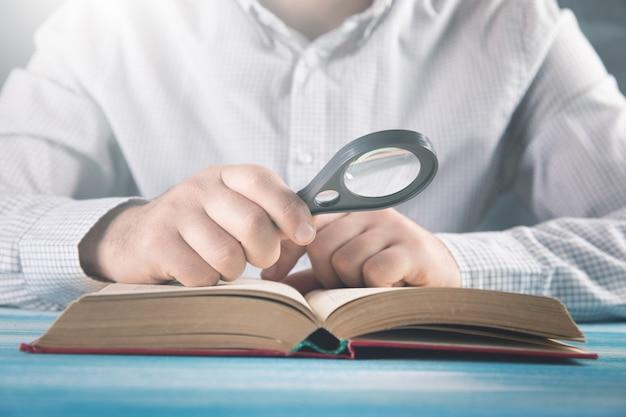 Uomo che legge un libro utilizzando una lente di ingrandimento