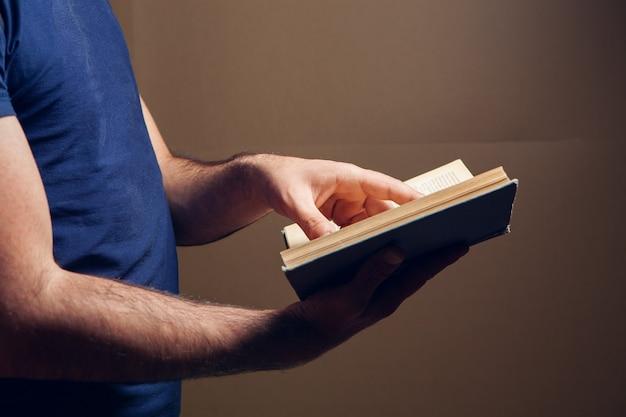Uomo che legge un libro in piedi su sfondo marrone