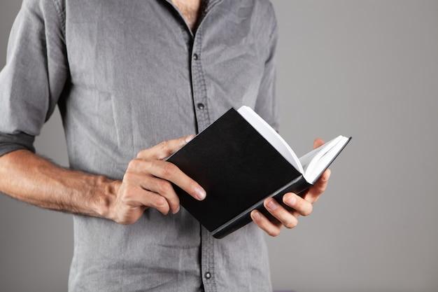 Uomo che legge un libro in piedi su sfondo grigio