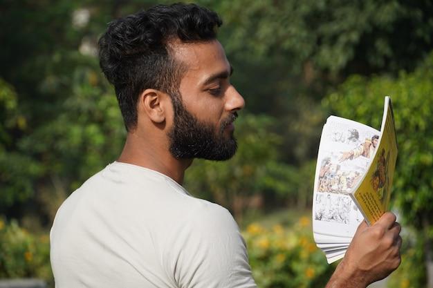 Un uomo che legge un libro con sfondo sfocato di vegetazione