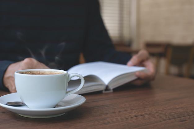 Uomo che legge un libro sul tavolo di legno al bar