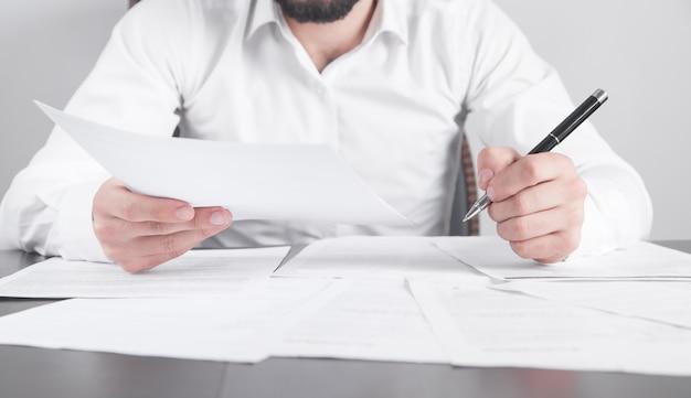 Uomo che legge il documento in ufficio. attività commerciale