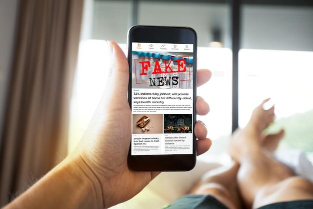 Uomo che legge notizie false o articoli su covid19 in un'applicazione sullo schermo dello smartphone