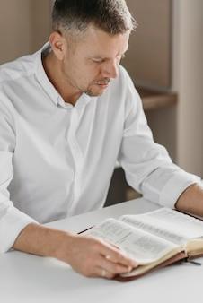 Uomo che legge un libro sacro sul tavolo