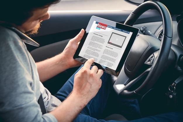 Uomo che legge notizie alla guida di un'auto con un tablet in mano
