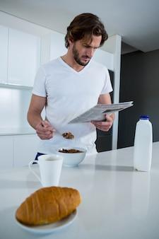 Equipaggi il giornale della lettura mentre mangiano la prima colazione in cucina