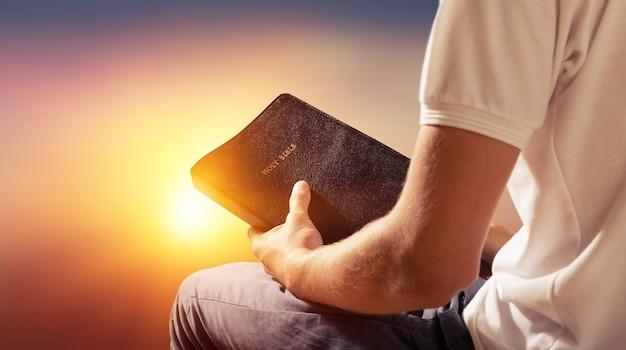 Uomo che legge il vecchio libro della bibbia sullo sfondo
