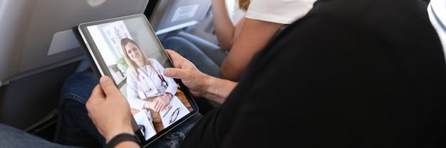 L'uomo riceve consulenza medica in videochiamata mentre è seduto sull'aereo