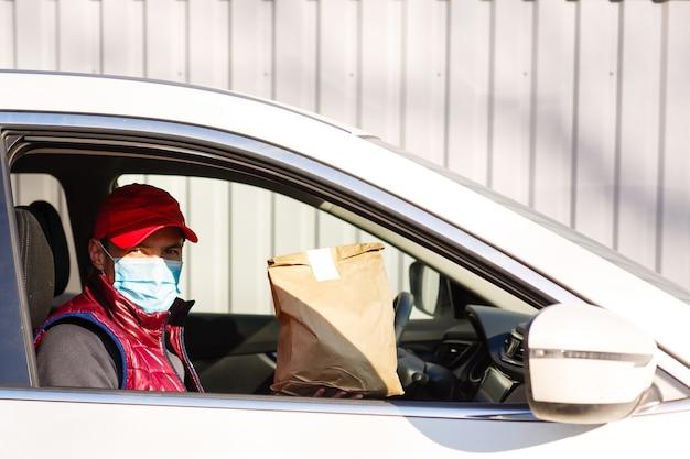 Uomo in berretto rosso che dà ordine di fast food. il corriere tiene il pacchetto di carta con il cibo. consegna prodotti dal negozio o ristorante a casa.