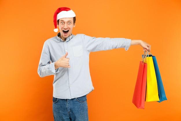 Uomo in berretto rosso con in mano molte borse colorate dopo lo shopping natalizio pollice in alto e sorriso a trentadue denti