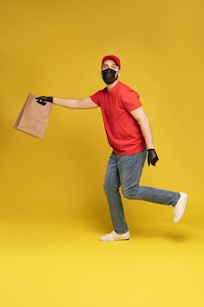 Uomo in berretto rosso, t-shirt in maschera protettiva e guanti che danno ordine di fast food isolato sulla parete gialla