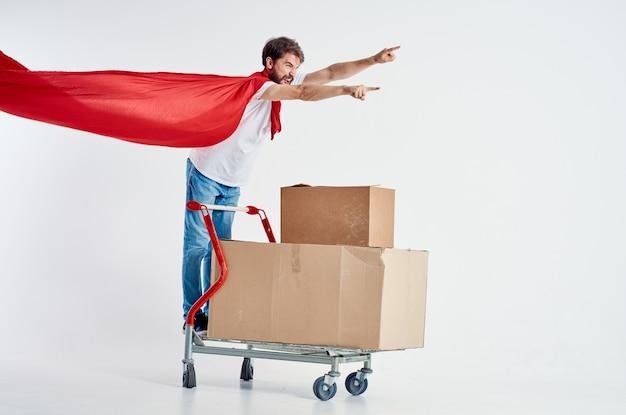L'uomo in un mantello rosso trasporta in una scatola isolata sullo sfondo