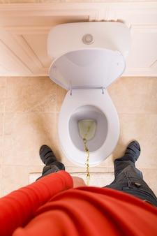 Uomo in giacca rossa che piscia nella toilette, vista dall'alto.