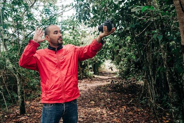 Uomo in giacca rossa che saluta la telecamera nel mezzo della foresta che registra un video con la sua macchina fotografica.