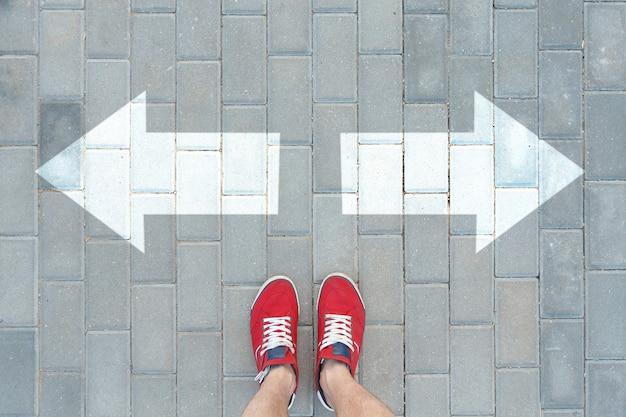 Un uomo con scarpe da ginnastica rosse si fermò davanti agli indicatori di direzione. concetto di processo decisionale.