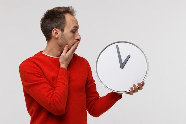 Uomo in maglione rosso che tiene grande orologio rotondo, sotto shock copre la bocca con la mano. mancanza di tempo