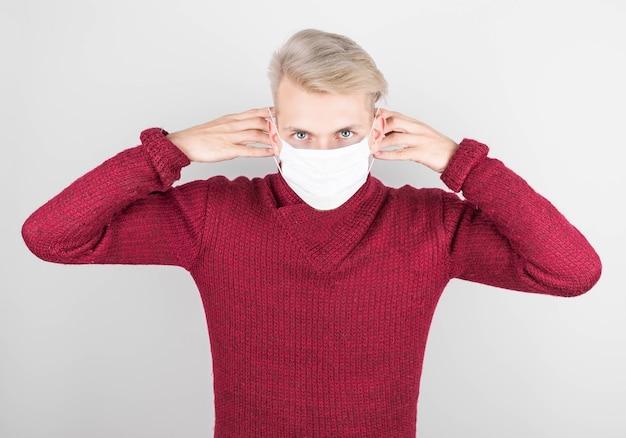 Un uomo con un maglione rosso indossa una maschera antivirus per impedire ad altri di contrarre il coronavirus covid-19 e sars cov 2