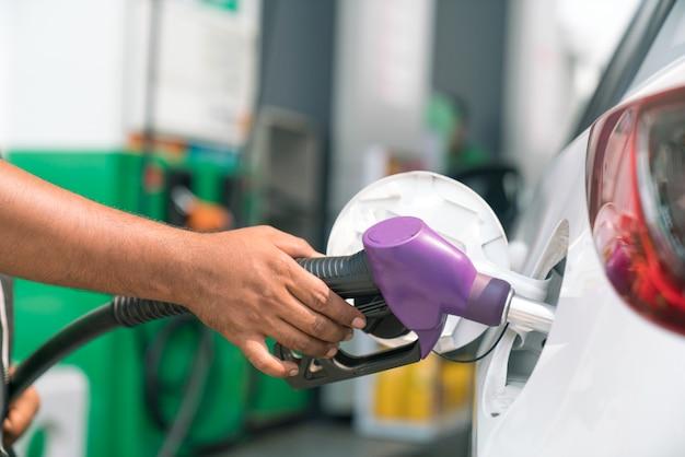 Uomo fare rifornimento di auto nella stazione di benzina per il viaggio