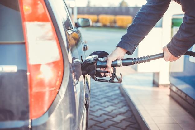 Uomo che fa rifornimento di carburante a un'auto durante le basse tariffe del carburante, i prezzi del carburante, il concetto di trasporto