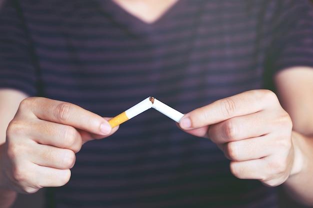 Uomo che rifiuta il concetto di sigarette per smettere di fumare e uno stile di vita sano sfondo scuro. o no smoking concetto di campagna.