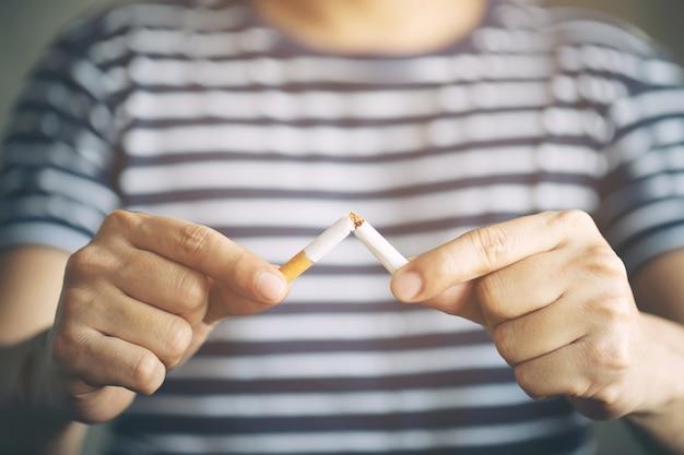 Uomo che rifiuta il concetto di sigarette per smettere di fumare e uno stile di vita sano sfondo scuro.