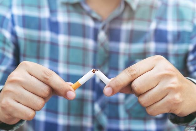Uomo che rifiuta il concetto di sigarette per smettere di fumare e uno stile di vita sano o concetto di campagna per non fumatori.